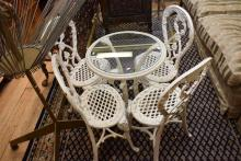 A VICTORIAN FIVE PIECE WROUGHT IRON WHITE PAINTED GARDEN SETTING WITH GLASS TOP