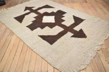 A VINTAGE BROWN AND CREAM FLOOR RUG - some stains