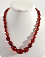 A STRAND OF FACETED AMBER BEADS