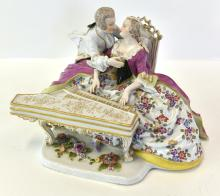 A PORCELAIN FIGURAL GROUP OF A COUPLE PLAYING PIANO