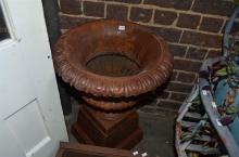 A RUSTIC CART IRON URN ON PEDESTAL (PLEASE NOTE: IF PURCHASED, THIS ITEM MUST BE REMOVED BY SPECIALIST CARRIERS AT THE CUSTOMERS E...
