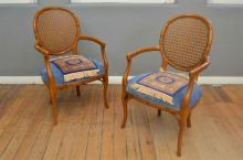 A PAIR OF RATTAN BACK BAMBOO EFFECT ARMCHAIRS WITH ACCOMPANYING PATTERNED COVERS