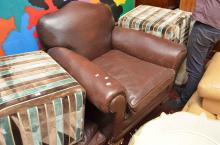 A CHOCOLATE BROWN LEATHER ARMCHAIR ON CASTERS (SOME WEAR AS FOUND)