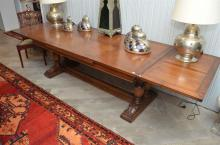 A LARGE FRENCH PROVINCIAL OAK EXTENDABLE DINING TABLE
