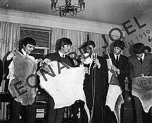 THE BEATLES HOLDING UP ANIMAL SKINS AT CONFERENCE/RECEPTION