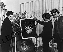 JOHN LENNON HOLDING PORTRAIT OF HIMSELF