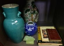 A SHELF OF ITEMS INCLUDING VASES AND REFERANCE BOOKS