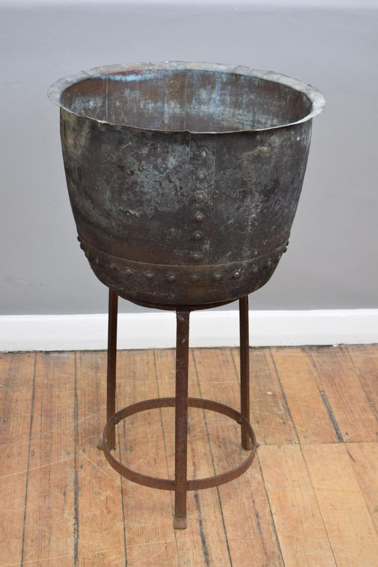 A 19TH CENTURY RIVETED COPPER BOWL ON IRON STAND