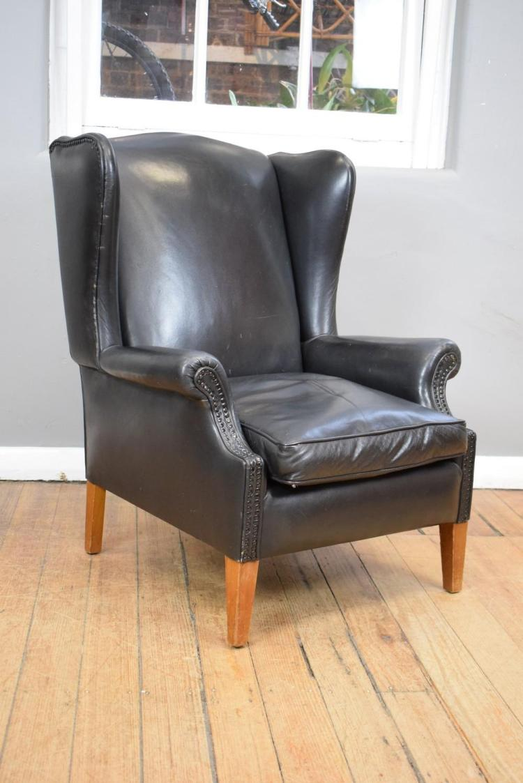 A LEATHER STUDDED WINGBACK ARMCHAIR