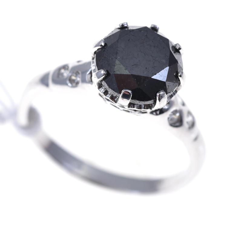 A SOLITAIRE BLACK DIAMOND RING WITH WHITE DIAMONDS SET TO THE SHOULDERS IN 18CT WHITE GOLD