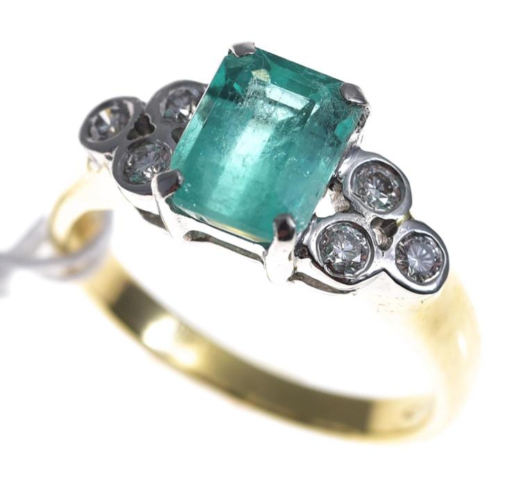 AN EMERALD AND DIAMOND RING SET IN PLATINUM AND 18CT GOLD