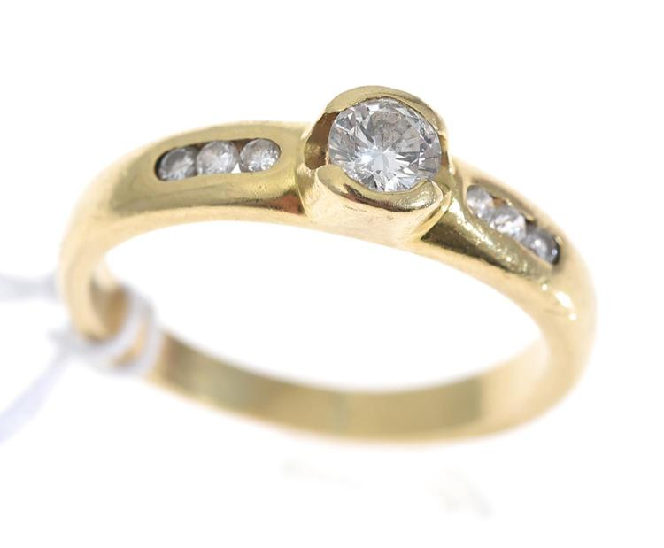 A BEZEL SET DIAMOND SOLITAIRE RING WITH DIAMOND SET SHOULDERS, IN 18CT GOLD