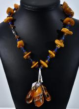 AN AMBER AND LAPIS LAZULI TUMBLED BEAD NECKLACE AND THREE AMBER PENDANTS