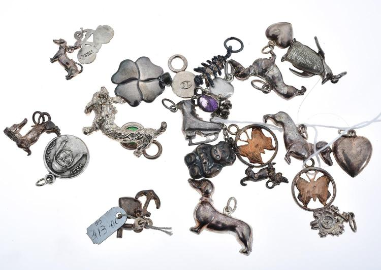 A LARGE COLLECTION OF STERLING SILVER CHARMS INCLUDING DOGS