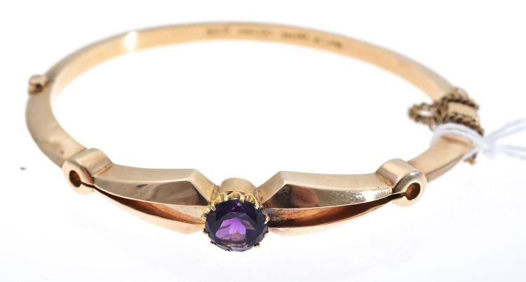 AN ANTIQUE 15CT GOLD AND AMETHYST SET HINGED BANGLE.