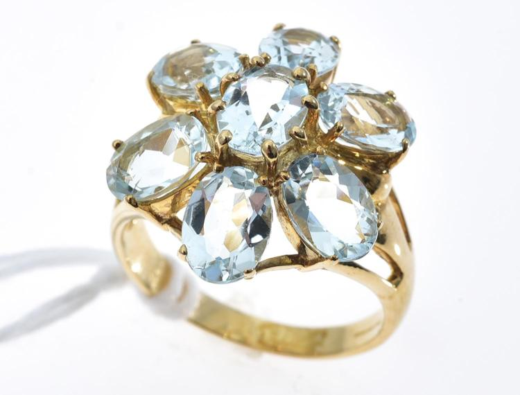 AN AQUAMARINE FLOWER RING MOUNTED IN 9CT GOLD