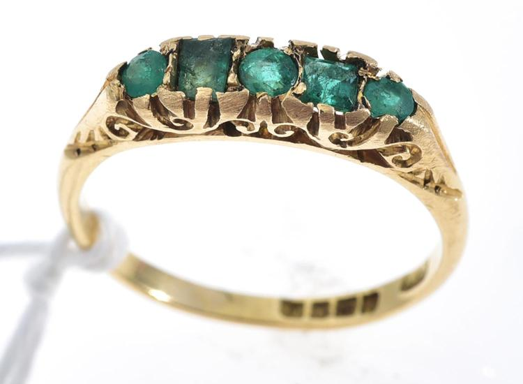 AN EMERALD HALF HOOP RING IN 18CT GOLD