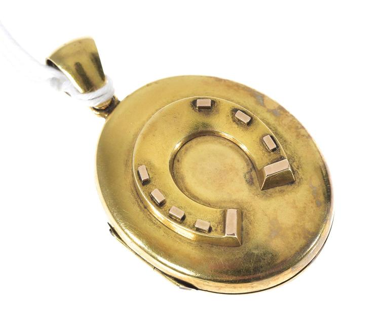 A VICTORIAN GOLD HINGED OVAL LOCKET WITH APPLIED HORSESHOE MOTIF SET IN 15CT GOLD.