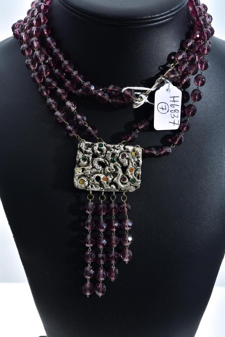 A MULTI-STRAND PURPLE GLASS BEAD NECKLACE WITH DECORATIVE CLASP