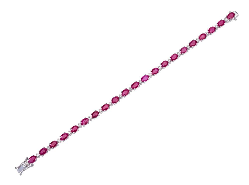 A RUBY AND DIAMOND LINE BRACELET - Comprising twenty one oval rubies totalling 14.30cts, spaced with round brilliant cut diamonds to...