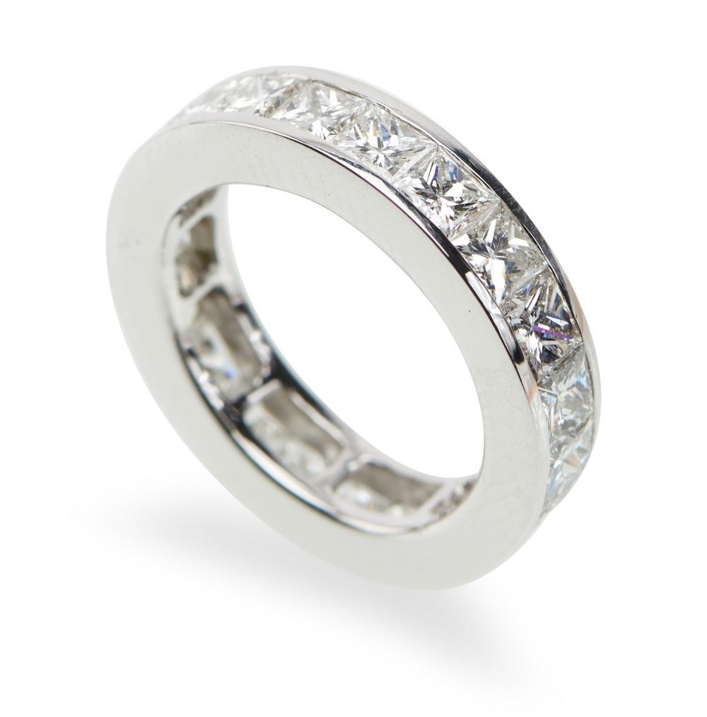 A DIAMOND ETERNITY RING - The full circle ring set with twenty one princess cut diamonds totalling 6.50cts, in 18ct white gold, ring...