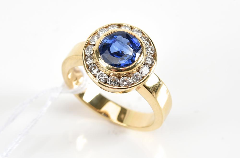 A SAPPHIRE AND DIAMOND CLUSTER RING IN 18CT GOLD, SAPPHIRE WEIGHING 1.46CTS