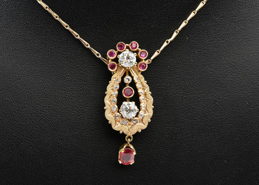 A SYNTHETIC RUBY AND DIAMOND PENDANT IN 9CT GOLD WITH CHAIN
