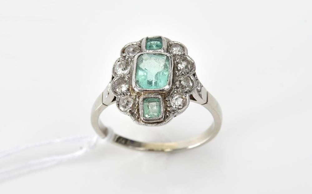AN EMERALD AND DIAMOND RING IN GOLD