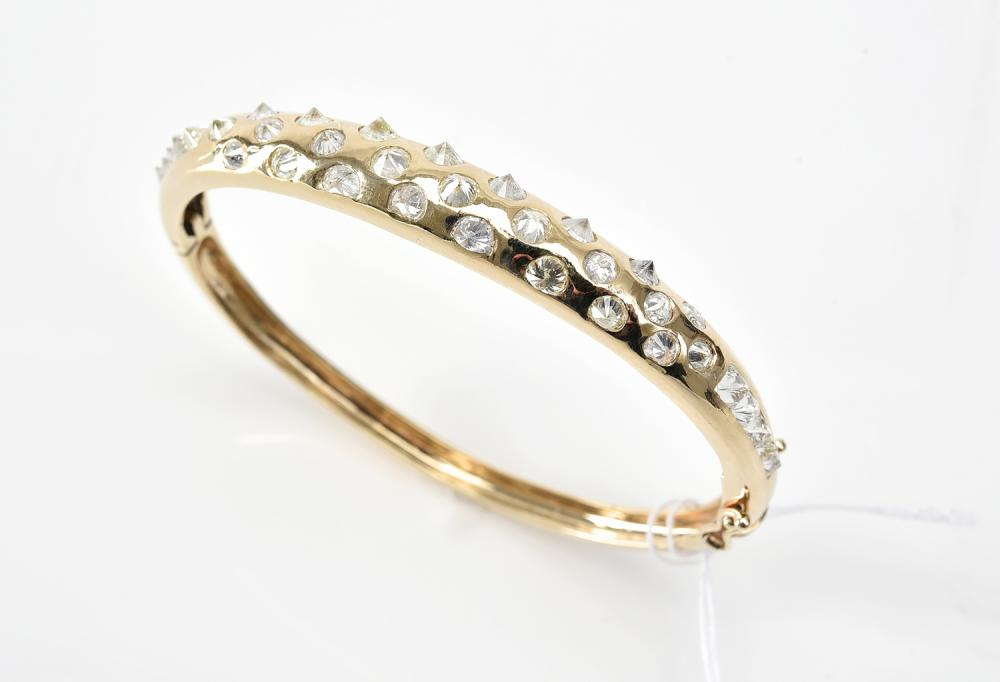 AN INVERTED DIAMOND BANGLE IN 9CT GOLD.