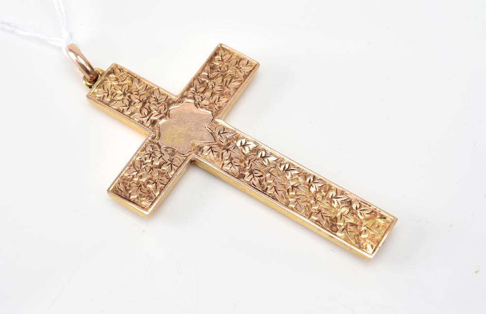 A CHASED CROSS IN 9CT GOLD.
