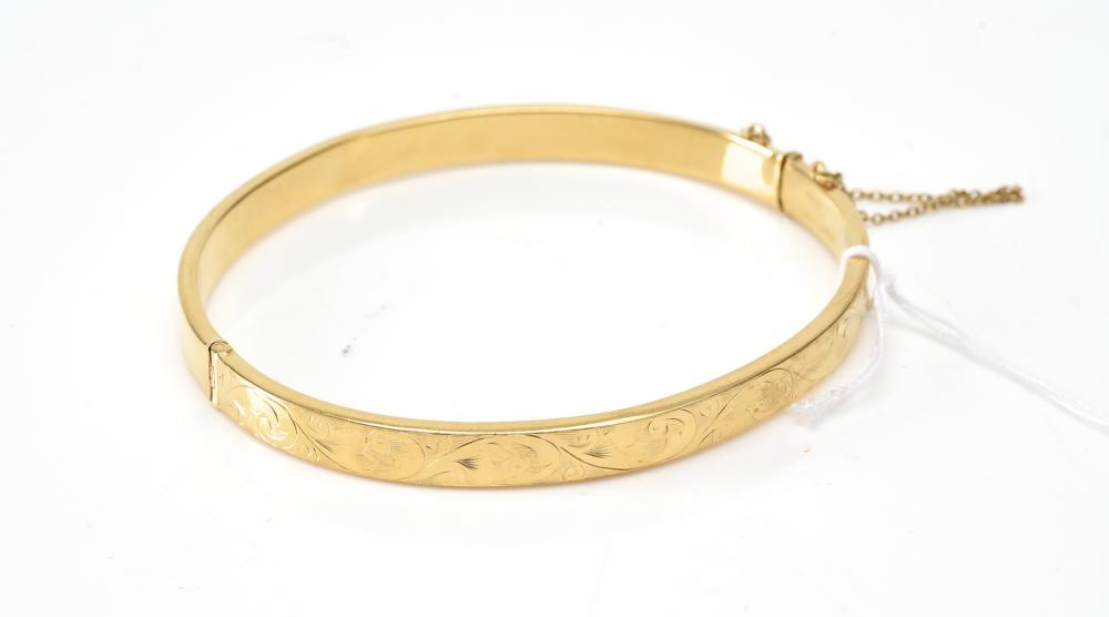 A SCROLL ENGRAVED HINGED BANGLE IN 9CT GOLD