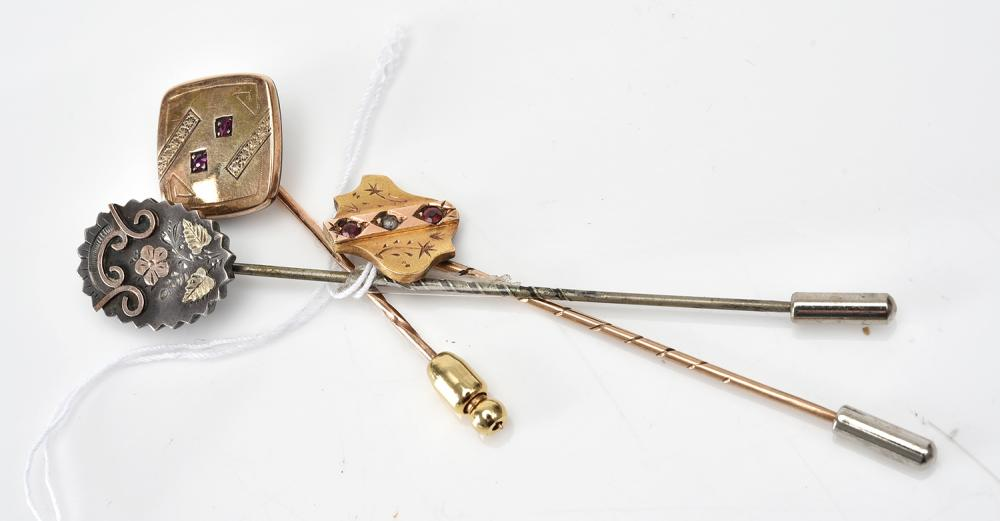 A COLLECTION OF THREE STICK PINS, TWO GEM SET IN GOLD, THE OTHER IN SILVER