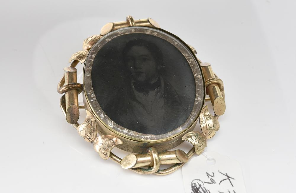 AN ANTIQUE GOLD CASED MOURNING BROOCH