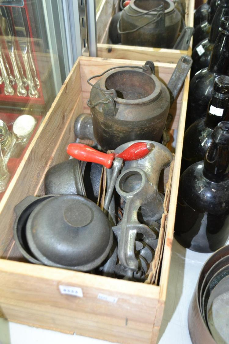 A BOX OF CAST IRONWARES AND GLASS BOTTLES