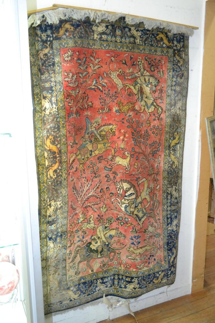 A PERSIAN SILK AND WOOL HAND WOVEN RUG WITH HUNTING SCENE AND ATTACHED HANGER