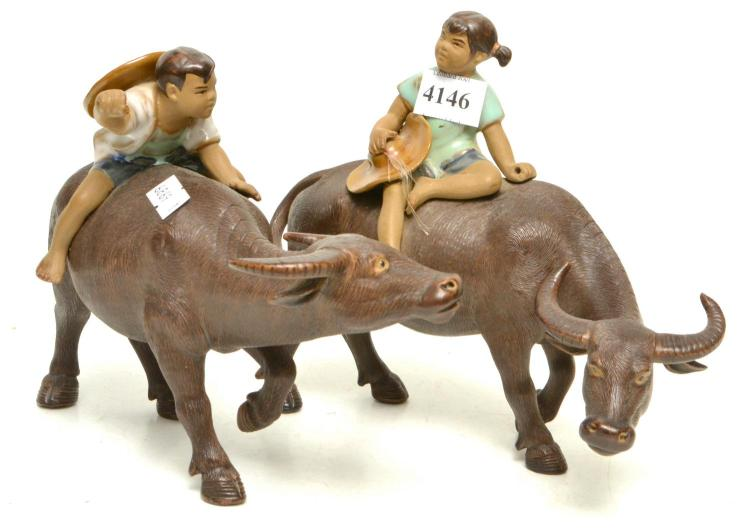 A PAIR OF CHINESE CERAMIC FIGURES OF MEN ON BUFFALO