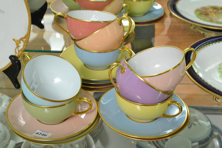 A LIMOGES TEA CUPS AND SAUCERS IN PASTEL TONES