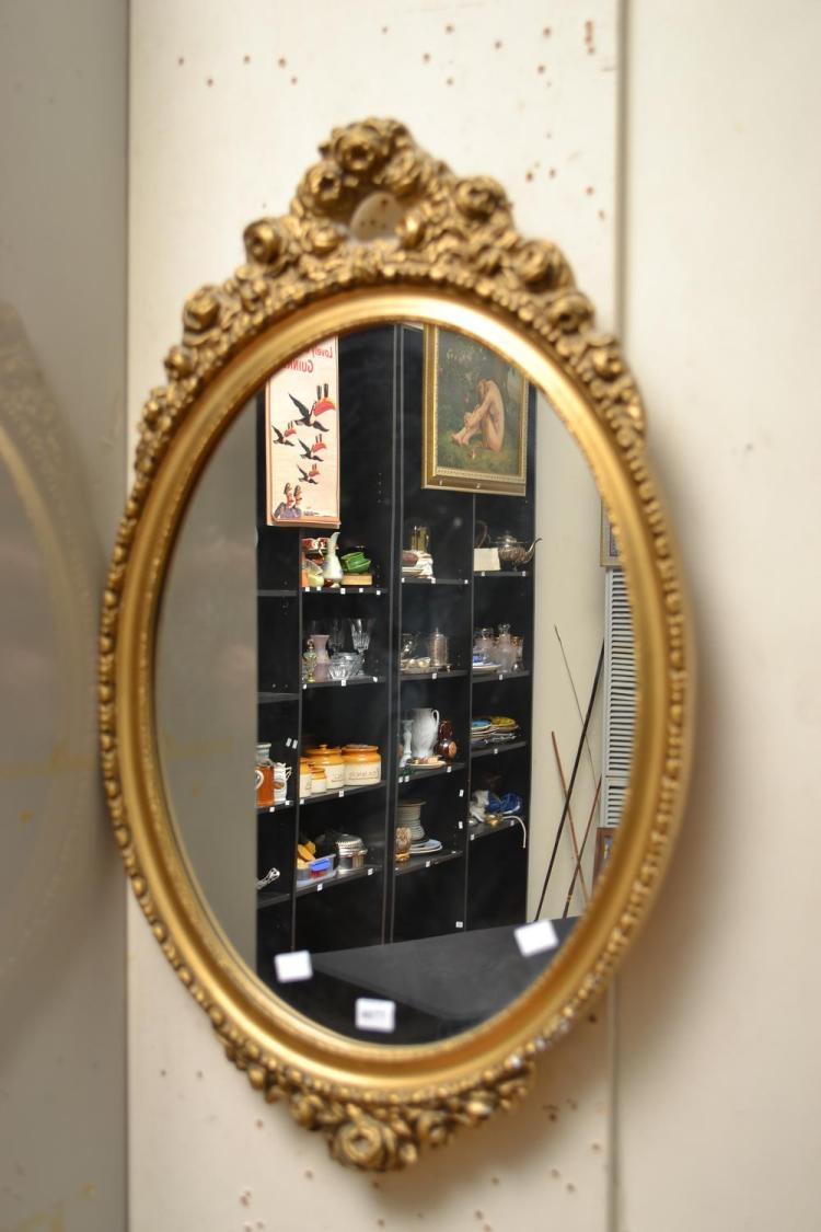 AN OVAL WALL MIRROR HOUSED IN A GILT FRAME