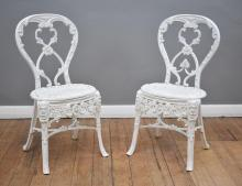 A PAIR OF VICTORIAN CAST IRON COALBROOKDALE GARDEN CHAIRS