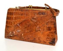 AN ALLIGATOR SKIN BAG WITH ALLIGATOR ON THE FRONT