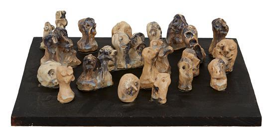 ATTRIBUTED TO MITZI FINEY (born 1930) Faces on a Board glazed ceramic on painted wood base