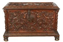 AN ANTIQUE FRENCH HEAVILY CARVED WALNUT COFFER. Depicting unusual mythological scenes. Bearing a heraldic shield to lid, 65.5cm high...
