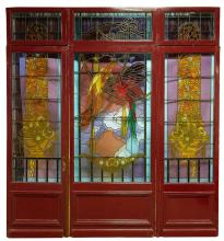 AN IMPRESSIVE THREE PANEL STAINED GLASS ENTRY DOOR. Colourfully depicting parrots and floriate designs. 295cm wide, 316cm high