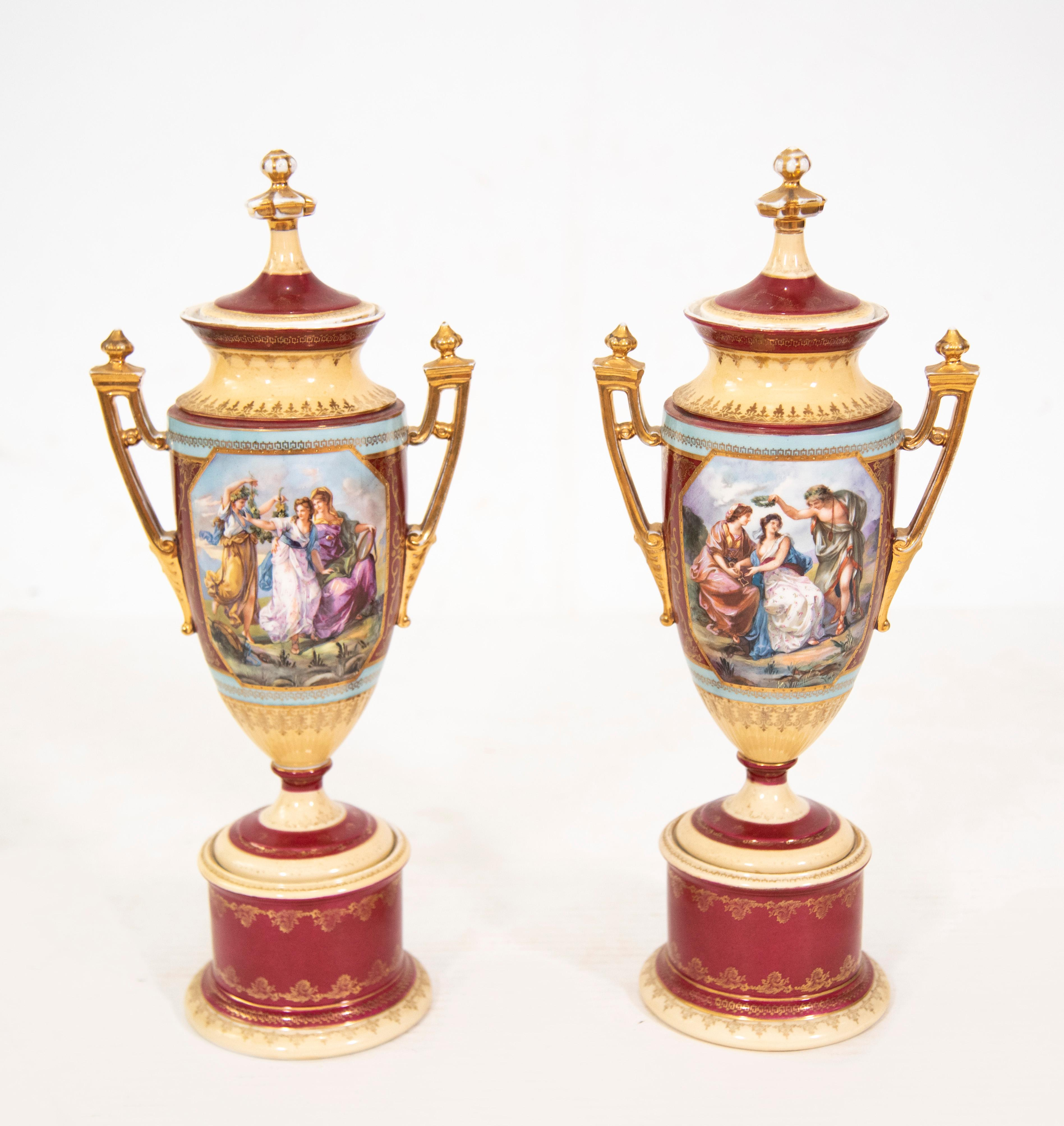 A Pair of Royal Vienna Covered Urns on Bolted Pedestals