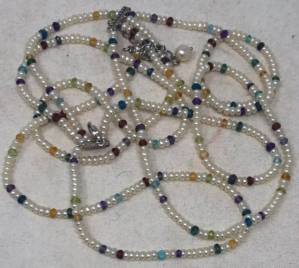 Four strand freshwater pearl necklace accented with emerald and garnet beads, length 15 inches.