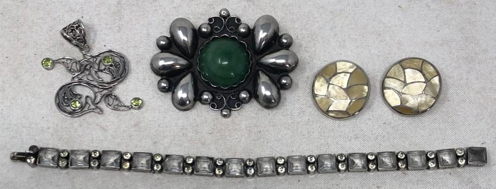 Group of sterling silver jewelry: silver and mother-of-pearl clip-on button earrings; Mexican silver and green stone brooch; silver filigree pendant with four peridot; silver fine bracelet with fifteen bezel set squar...