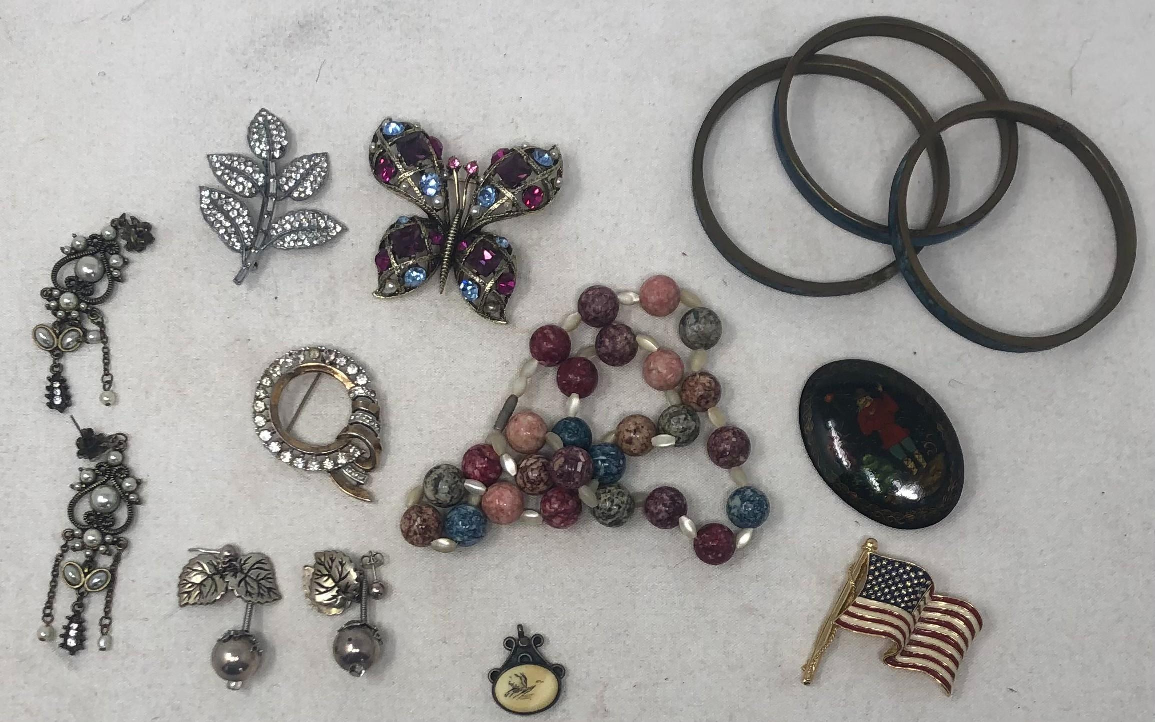 Group of costume jewelry including: Ciner colored rhinestone butterfly brooch; Indian inlaid bangle bracelets (3); Marble stone beads; Sterling Silver hanging earrings; Scrimshaw and silver pendant; Ciner American fla...