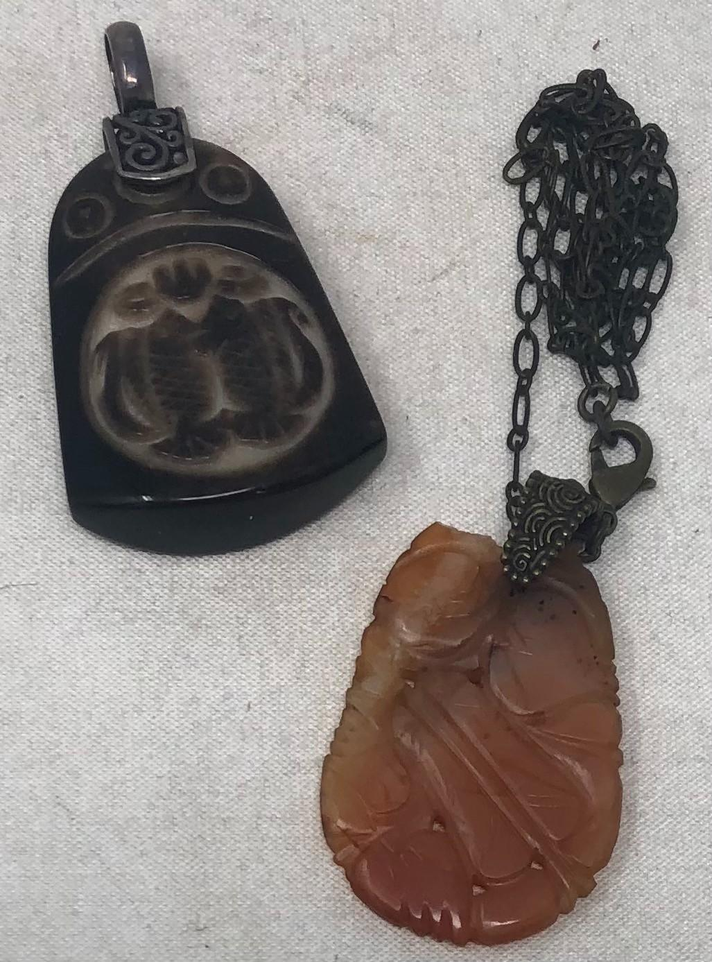 Two large Vintage Carved Pendants; carved orange brown Jadeite pendant, 2 x 1 1/4 inches (chipped at top) on chain; other carved heavy dark brown glass with Asian design carving, 2 x 1 1/2 inches.