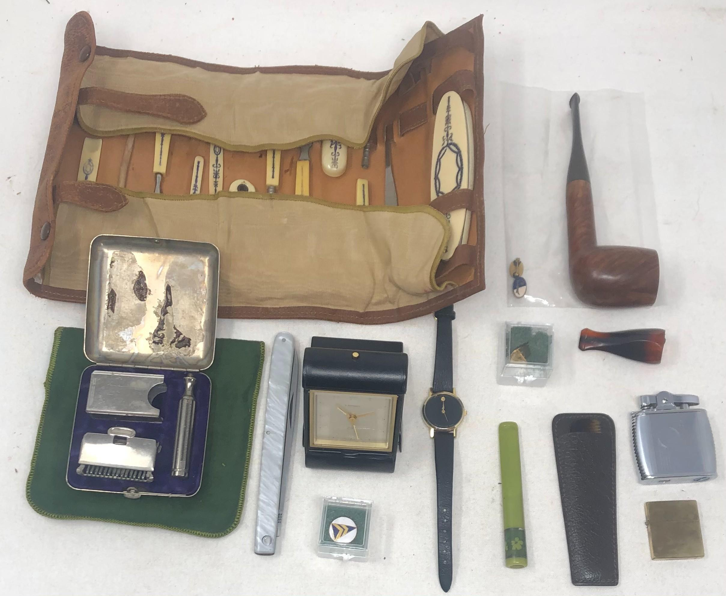 """Gentleman's vanity group including: T. Anthony travelling clock in leather case; English pipe, G.A. Georgopulo; two yacht club insignia pins; cigar and cigarette holders; wrist watch marked, """"MOVADO""""; Ronson Viking li..."""