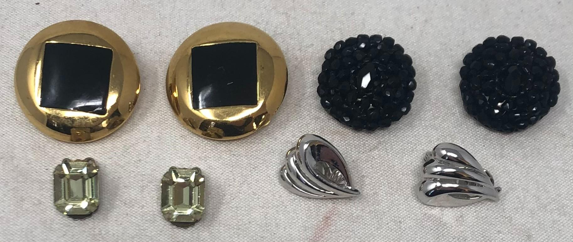 Four pair vintage costume earrings: St. John 1980's gold tone and black enamel large round button style clip earrings; Liz Claiborne jet button clip on earrings; Monet silver tone wing shape clip-on earrings; Vintage ...